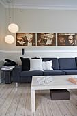 Dunkelgraues Polstersofa, darüber Fotoreihe, Pendelleuchten und Couchtisch auf hellem Dielenboden im Wohnzimmer