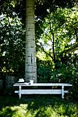White wooden table below tree in garden
