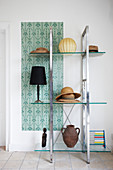 Hats, table lamps and urn on glass shelves