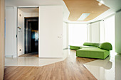 Green modular sofa in living room with direct access to lift