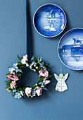 Blue-and-white wall plates and a wreath of spruce sprigs and spring flowers