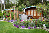 Allotment garden with garden shed, tool shed, shrub bed and rose arch