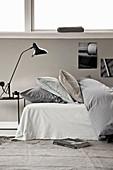 Bett mit Bettdecke und Kissen, Nachttisch mit Leselampe