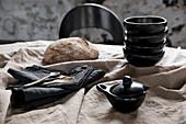 Black crockery, black napkins and bread on a beige linen tablecloth