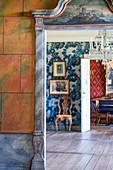 Blick durch Türrahmen mit Malerei auf alte Fotos und Stuhl vor Wand mit Tapete