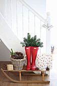 Wellie boots decorated with fir sprigs on a sledge against a flight of stairs