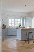 Offene, blaugraue Küche mit Frühstückstheke