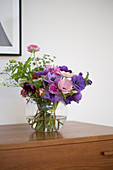 A bouquet of anemones in a glass vase on a chest of drawers