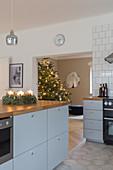 Adventskranz auf graublauer Kücheninsel mit Holzarbeitsplatte, im Hintergrund Weihnachtsbaum