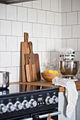 A kitchen corner with a wooden worktop, chopping boards, a food processor and a fruit bowl