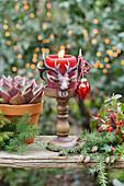 A deer candlestick with a red candle placed outdoors