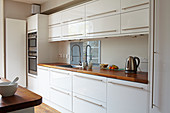 White fitted kitchen with wooden worksurface