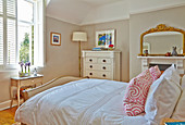 Doppelbett, weiße Kommode und Kamin mit Spiegel im Schlafzimmer