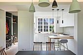 Blick über Esstisch auf weiße Einbauküche mit Frühstückstheke