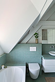 Bathroom in the attic with turquoise tiles