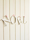 Decorative letters 'NOEL' on a red and white string in front of a white wooden wall