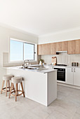 Island counter and bar stools in bright kitchen