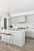 Island counter and bar stools in modern kitchen in shades of grey