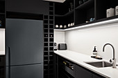 Fridge in black kitchen with white splashback