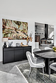 Modern artwork on wall above sideboard and dining area in foreground