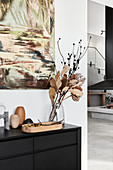 Modern artwork on wall above vase of dried branches on sideboard
