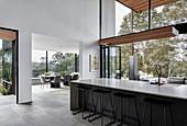 Lange Kücheninsel mit Barhockern in hohem Raum mit Glasfront