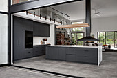 Black kitchen with island counter in open-plan interior with gallery level