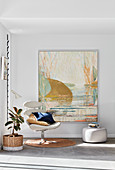 White swivel chair and pouffe below painting in corner