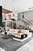 White sofa combination in high-ceilinged open-plan interior with staircase and gallery level
