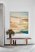 Vase on wooden bench below painting on wall of foyer