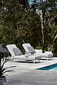 Comfortable loungers next to swimming pool