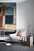 Armchair and side table next to modern artwork on wall