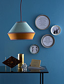 DIY picture frames made from plates, in the foreground a coffee table with decorative objects and a pendant lamp