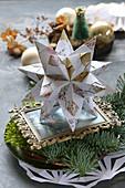 Tischdekoration mit Bascetta-Stern, selbstgefaltet aus Origami-Papier, auf Teller mit Moos