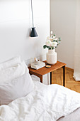 Bett, Nachttisch mit Blumen und Pendelleuchte vor weißem Raumteiler