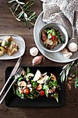 Salat auf schwarzer Platte und im Schälchen