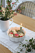 Bowl with candle and ranunculus flowers, bouquet of waxflower, eucalyptus
