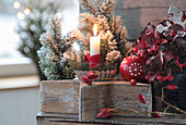 Candles in baking molds on a wooden star, Christmas tree ball, Christmas tree and rose hips
