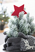 Tiny Christmas tree with a red star and knitted gloves