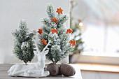 Tiny Christmas tree with stars made of orange peel, ceramic deer and cones