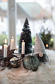 Iron basket as an Advent wreath with Christmas tree balls, zinc star, gnomes and trees