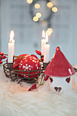 Metal basket as an Advent wreath with red and white Christmas tree baubles, rose hips and ceramic houses