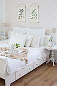 Weißes Bett mit Kissensammlung, Tablett und Tulpenstrauß