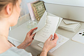 Blonde woman reading letter at desk