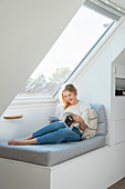 Blonde woman sits on bench in front of skylight
