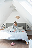 Blonde woman sitting with book on bed in attic room