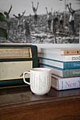 Kaffeebecher vor Bücherstapel und Retro Radio