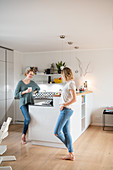 Two friends are standing at the kitchen counter in the open living room