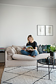 Blonde woman sitting on the sofa with magazine
