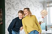 Zwei Freundinnen stehen lachend im Wohnzimmer
